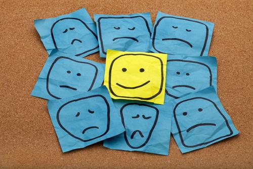 vários rostos tristes e um rosto feliz